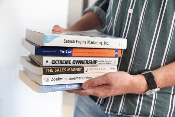 Man holding books building the fundamental skills of a growth hacker